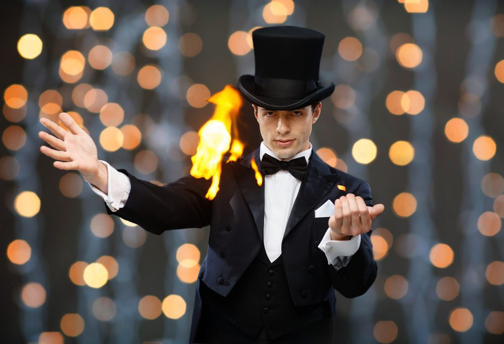 A magician stands in front of a curtain of lights while performing a trick